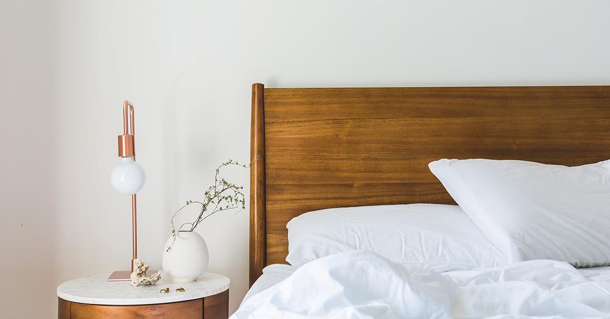 minimalisticka spalna s postelou vankusom s nocnym stolikom